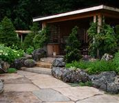 Weathered Limestone boulders retaining raised beds beside a random flagstone patio