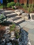 Wiarton guillotined steps with Weathered Limestone boulders and New York square cut flagstone patio