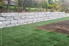 An Orillia armourstone retaining wall holding back an embankment