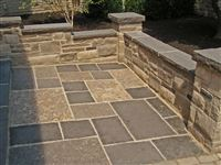 Ebel Black rockfaced coping on freestanding garden wall around a square cut flagstone patio