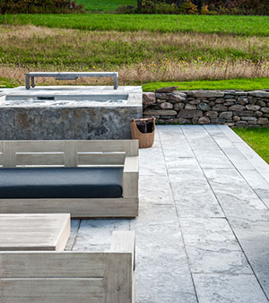 custom linear flagstone patio with hot tub and drystone wall