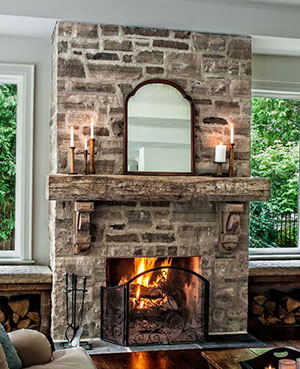 interior stone fireplace with rustic wooden mantel