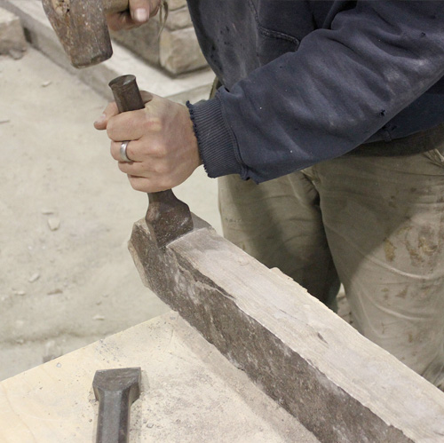 hand-dressing natural building stone with a mallet and mason's chisel