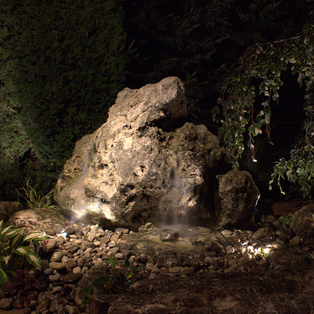 well-lit Weathered Limestone drilled rock water feature at night